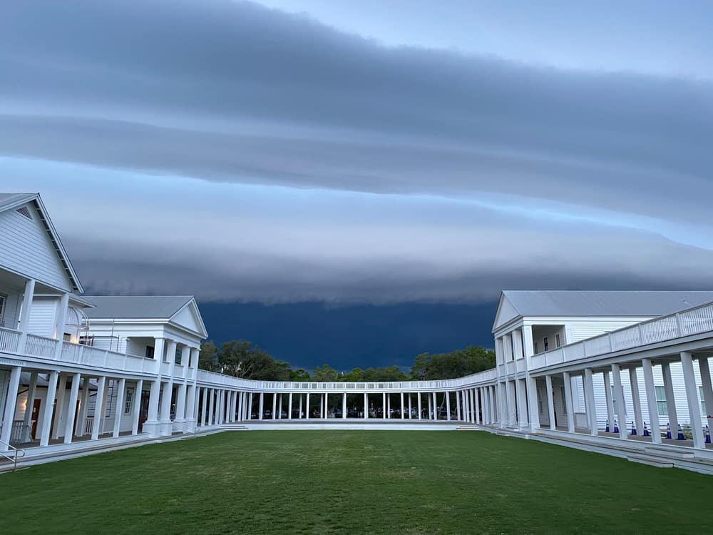 The grassy lawn in front of the amphitheater, surrounded by a columned walkway and buildings in Seaside, Florida.