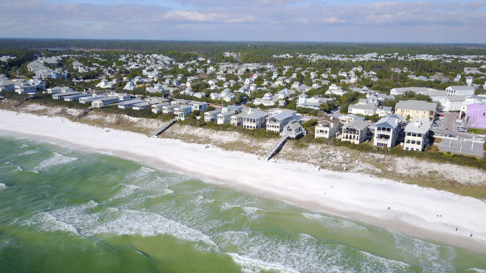 Rows of houses along a sandy beach in Seaside, Florida.