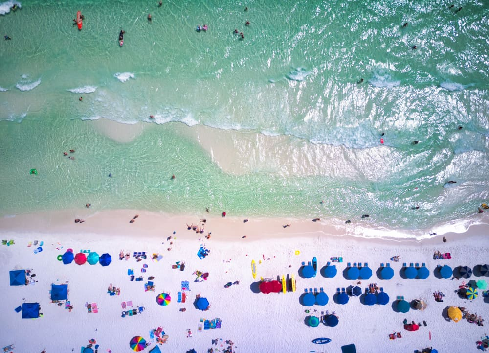 A view of beaches in Panama City from overhead with sand, water, and beach umbrellas