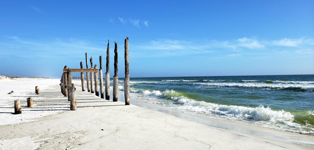 old broken wooden pier on shell island beach