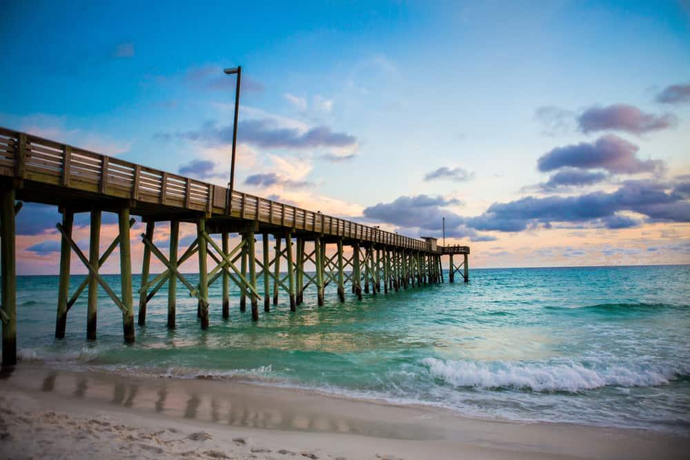 wooden pier extending into emerald water on beach