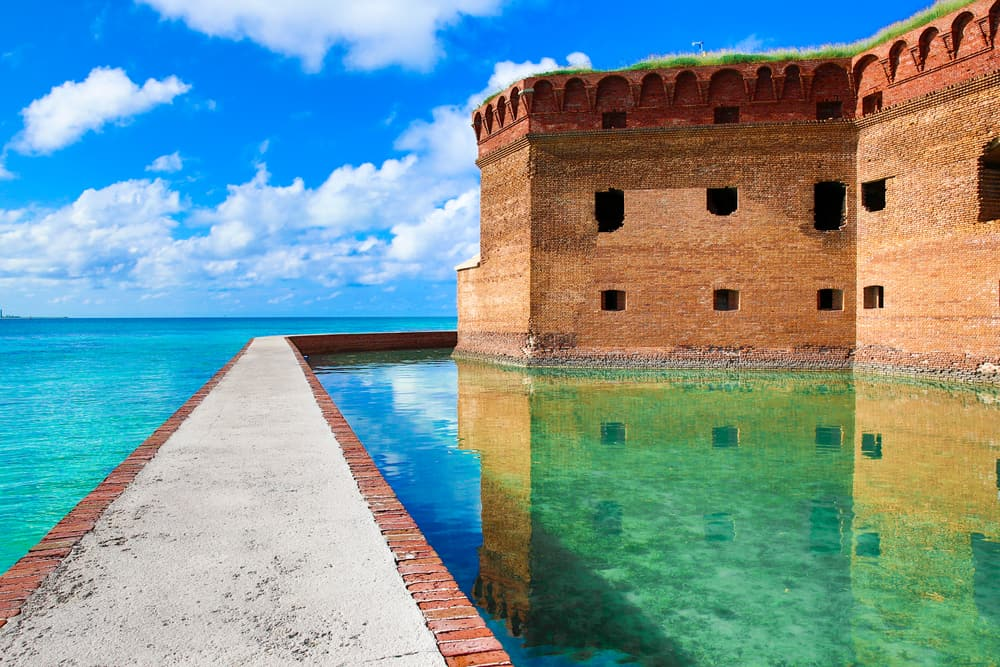 The walkway to Dry Tortuga's is made of brown stone and is a strong contrast to the blue waters that lead to the fort itself.
