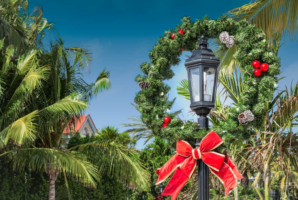 Key West in December features large decor, like this giant wreath with a large red bow, pinecones and more!