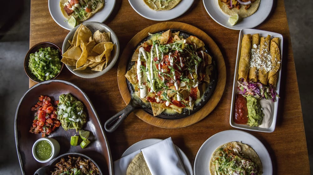 A table full of Mexican dishes, such as loaded nachos, table made guacamole, flaurtas, tacos, and fajitas