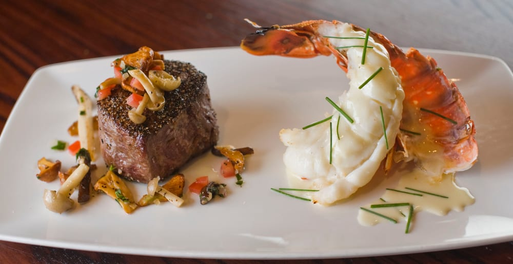 A surf and turf, the steak is topped with mushrooms and the lobster tail in a butter sauce
