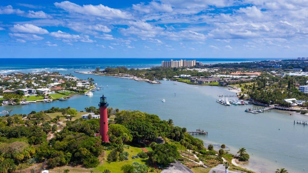 The beautiful city of Jupiter with the red lighthouse in the foreground, along with the intercostal leading out to the ocean