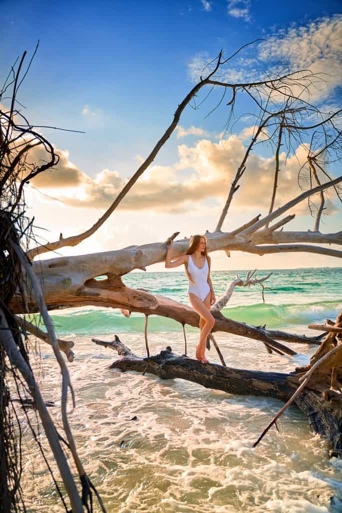 Standing on driftwood on Beer Can Island, one of the best beaches in Sarasota.