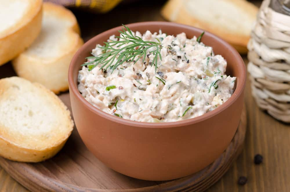 brown bowl filled with smoked fish dip on a wooden plate with bread on it
