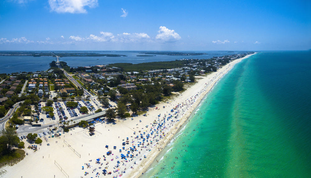 An aerial view of Anna Maria Island in Florida. You can see umbrellas and people on the beach, white sands, crystal blue water, and buildings.