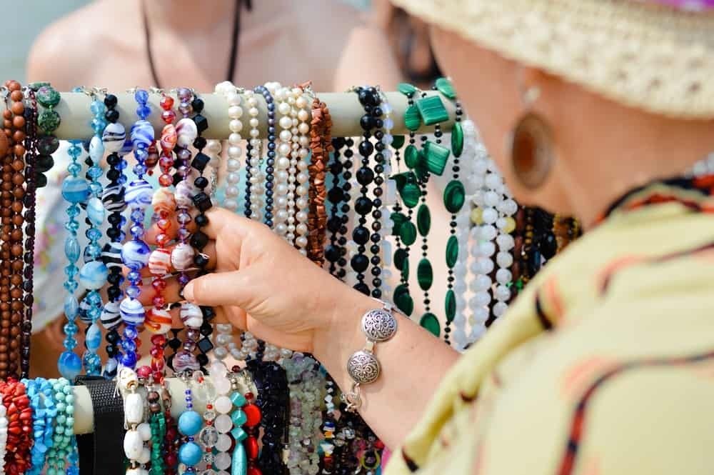 A person looking at a selection of shell and stone beaded necklaces and an outdoor market. The person is holding a few of the necklaces in their hand on the stand.