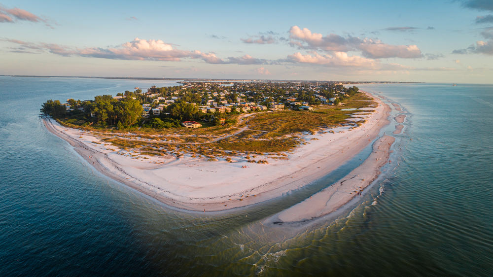 An aerial photo of the somewhat secret beach that is one of the best things to do in Anna Maria Island. The beach is at the very end of the island and in the distance you can see a town.