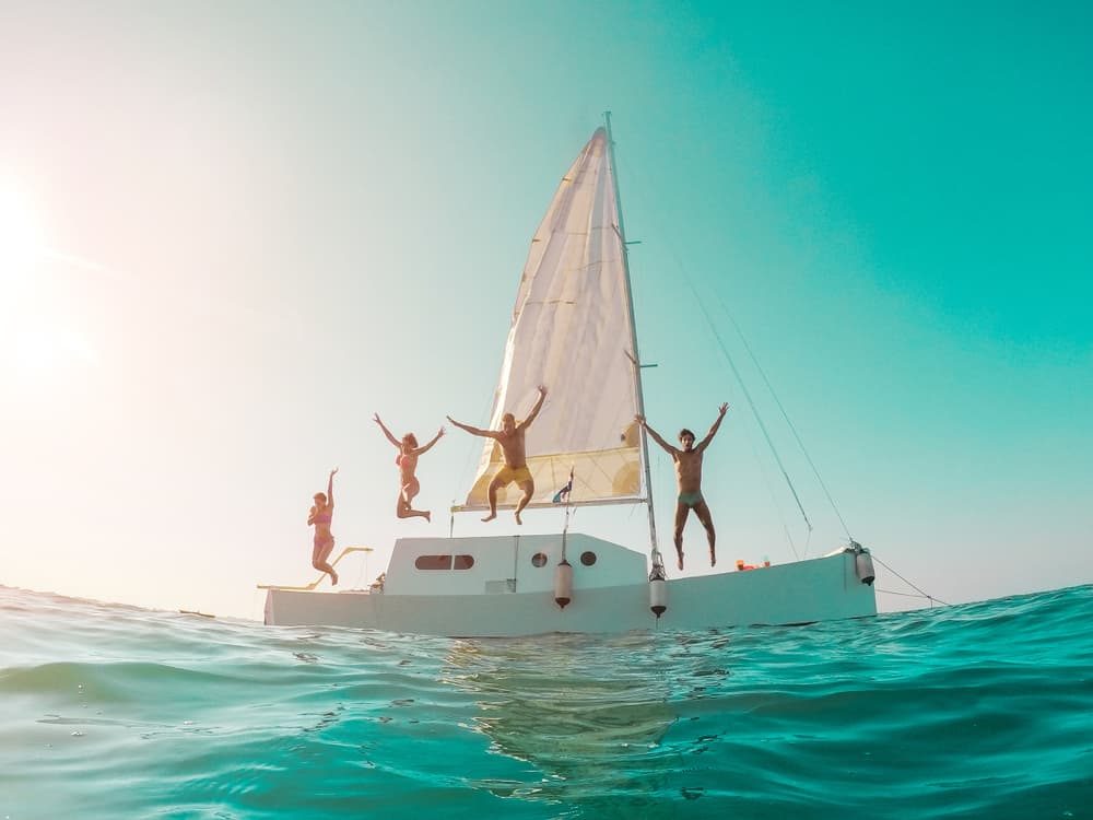People jumping off of a boat into the ocean as the sun starts to set. The boat is white with a white sail and the water and sky is very blue.