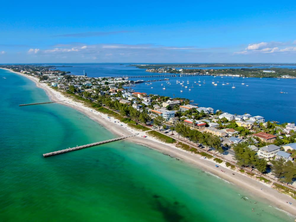 An aerial view of a beach town on Anna Maria Island. You can see large beach houses, two piers going out into the ocean, and on the other side of the island you can see boats in the ocean.
