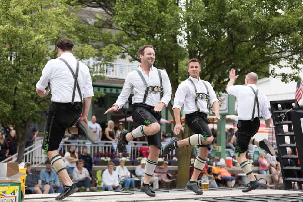 Bavarian dancers doing a performance at an Oktoberfest fair.