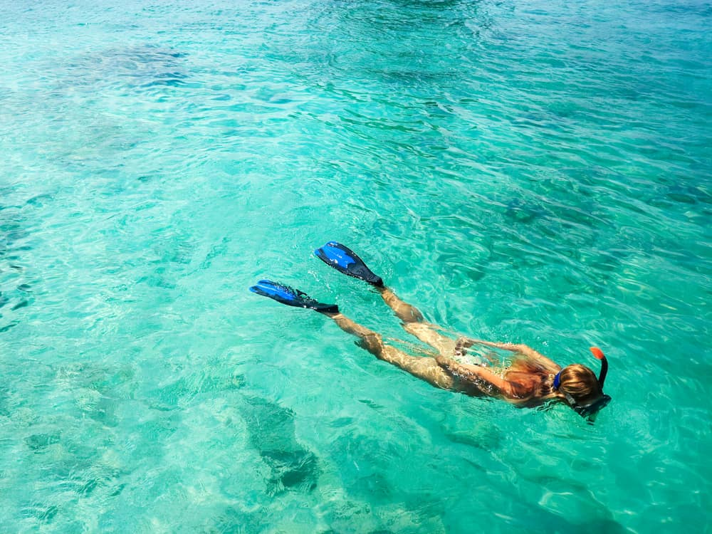 A person with long hair snorkeling in crystal blue water. They have on blue snorkeling flippers and a black and orange snorkel.