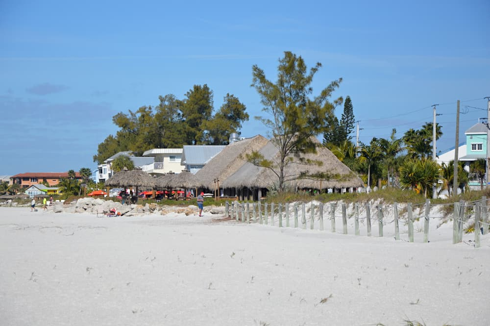 Looking at the rooves and other buildings of a small town on the edge of a sandy beach. You can see thatch rooves, colorful buildings, and trees.